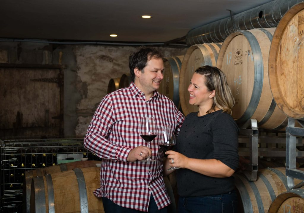 couple clinking wine glasses in front of barrels